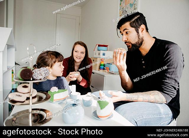 Girl having tea party with parents