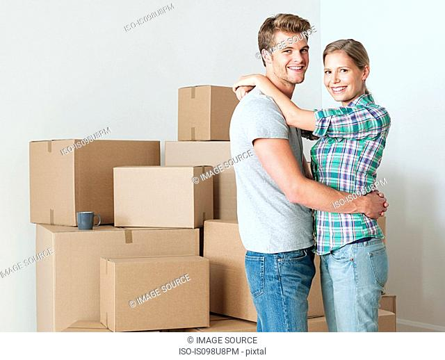 Young couple hugging by cardboard boxes