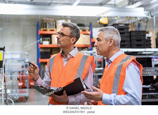 Two colleagues in factory hall wearing safety vests holding clipboard