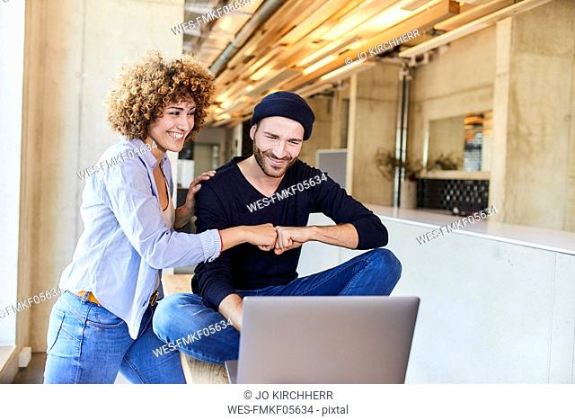 Happy man and woman with laptop fist bumping in modern office