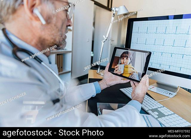 General practitioner talking with patient on video call through digital tablet at doctor's office