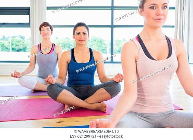 Women sitting in easy yoga pose in fitness studio