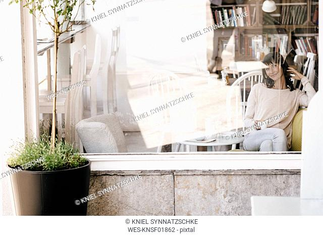 Woman in cafe, drinking coffee
