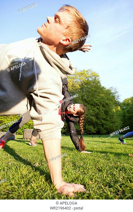 Young man and woman exercising in park