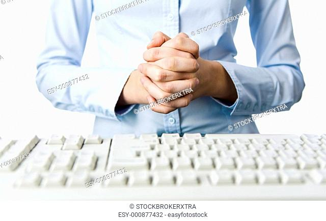 Image of female hands put together before her waist and with keyboard in front