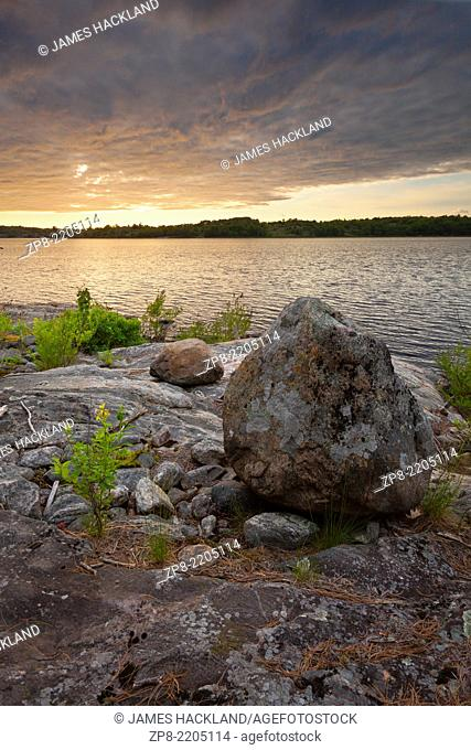 Sunset over lichen covered rocks along the shores of Georgian Bay. The Massasauga Provincial Park, Muskoka, Ontario, Canada