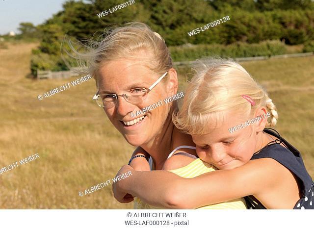 France, Bretagne, Landeda, Mother carrying daughter piggyback
