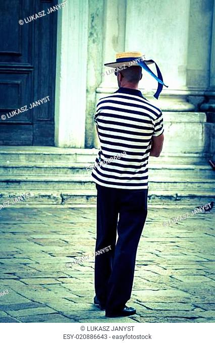 Gondolier on the docks awaiting tourists in Venice, Italy