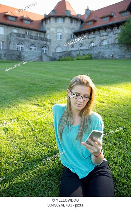 Young woman sitting on grass using smartphone