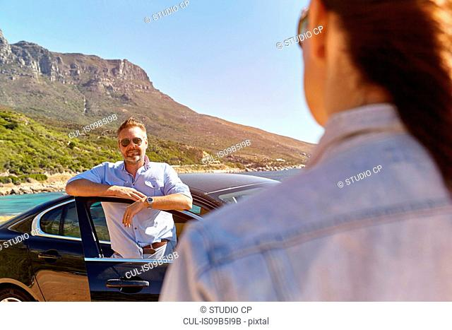 Man standing by open car door, woman walking towards him
