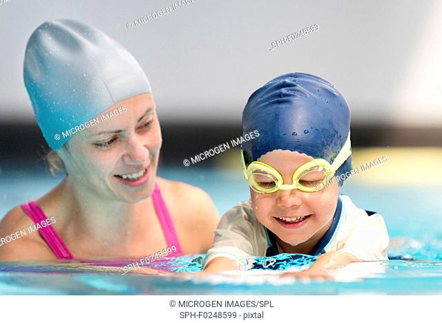 Swimming lesson, cute child and instructor in swimming pool