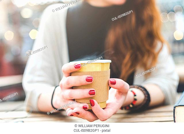 Cropped view of woman holding disposable cup, London, UK