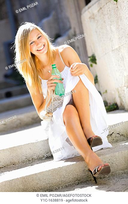 Happy young woman with a bottle of drinking water in hand