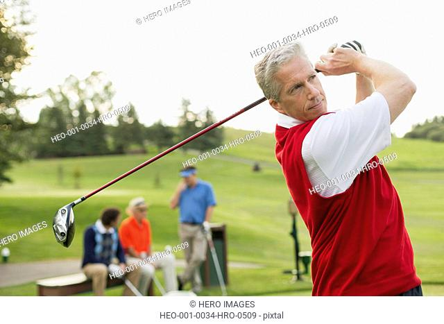 middle-aged man driving the ball on golf course