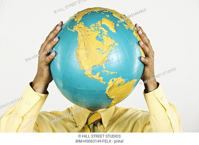 Native American businessman holding globe in front of face