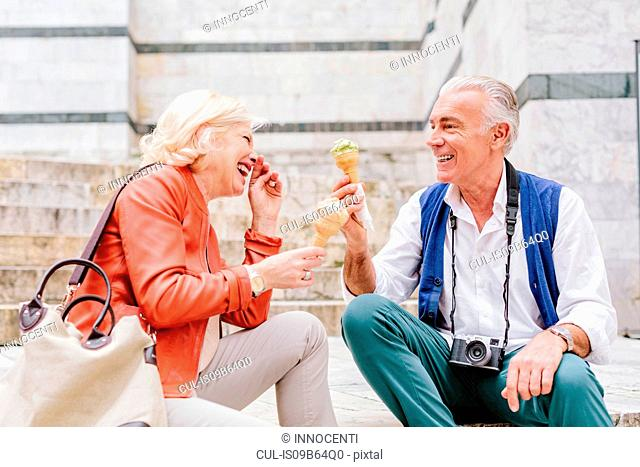 Tourist couple eating ice cream cones and laughing in Siena, Tuscany, Italy