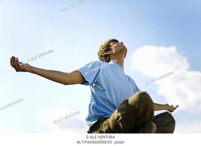 Young man meditating outdoors, holding yin yang balls