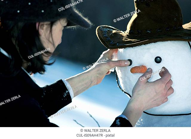 Mature woman placing the eyes on a snowman face