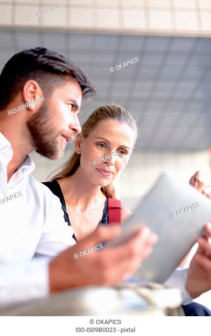 Mature man and woman sitting outdoors, looking at digital tablet