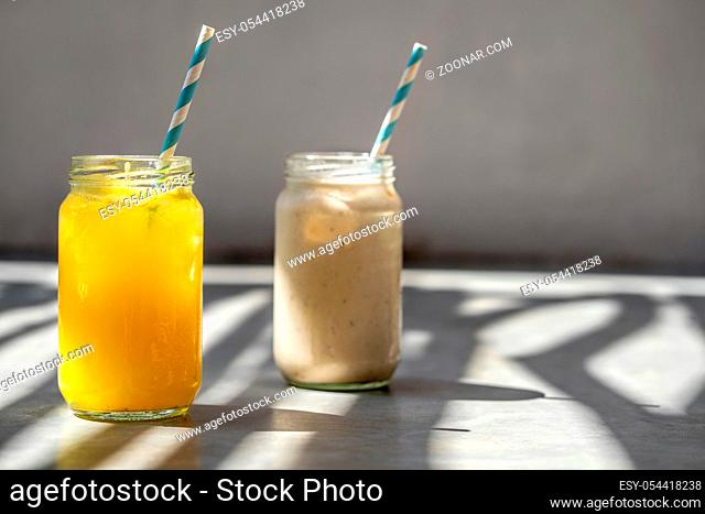 Two colorful cocktails with fruit slices in glass jars with white-cyan straws on the gray table. Sun shines onto them. Closeup. Horizontal