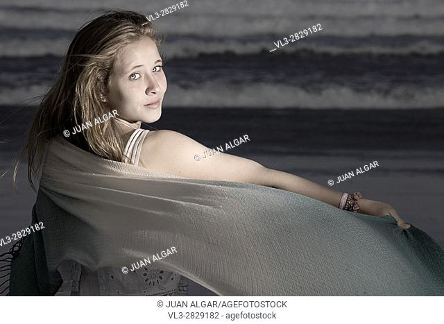 Young female standing on a beach and looking at camera over her shoulder. Horizontal outdoors shot