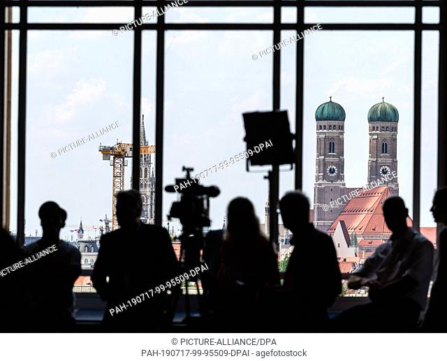 17 July 2019, Bavaria, Munich: During the session of the Bavarian state parliament, journalists wait at the large window in front of the backdrop of the state...