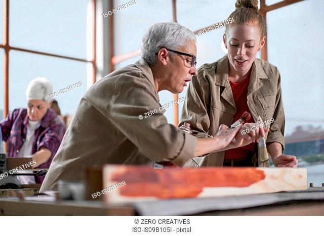 Mature female carpenter showing wood stain to trainee in furniture making workshop
