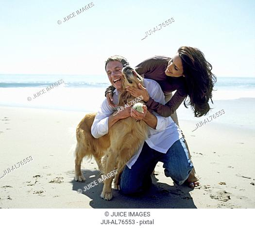 Portrait of a young couple playing with golden retriever on the beach