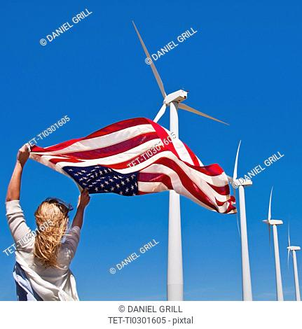 USA, California, Palm Springs, Woman weaving American flag with wind turbines in background