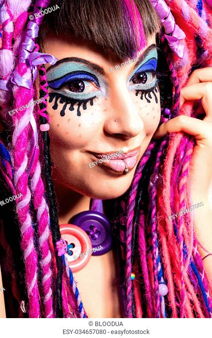 Portrait of a stylish young woman with multicolored dreadlocks and with stylish make-up in doll style. Creative make-up.Fantasy dress