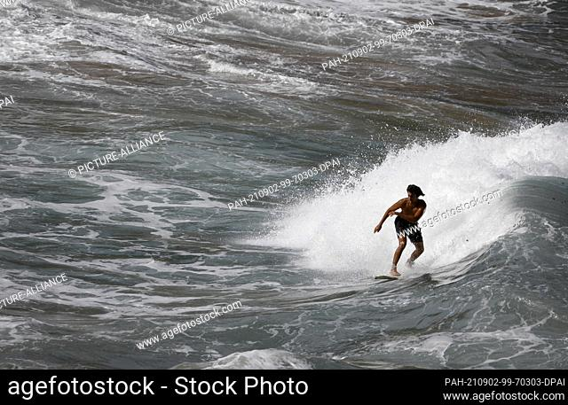 02 September 2021, Spain, Manacor: A surfer rides a wave at Cala Mendia in Manacor, Mallorca. Two young holidaymakers from North Rhine-Westphalia have drowned...