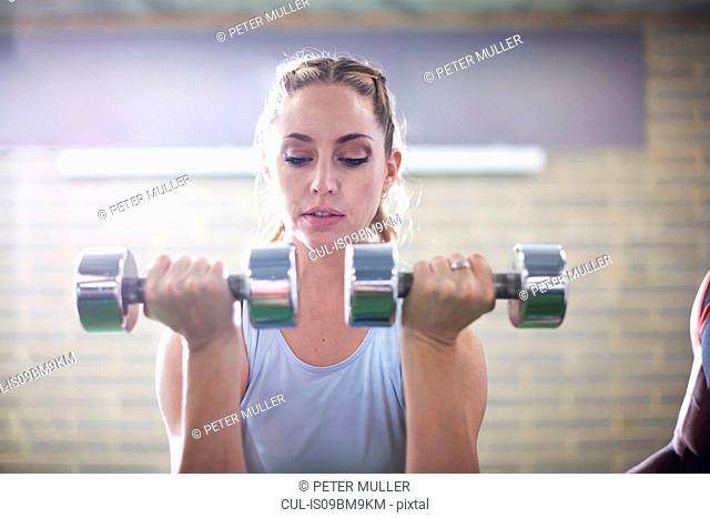 Trainer watching female client lifting dumbbells in gym