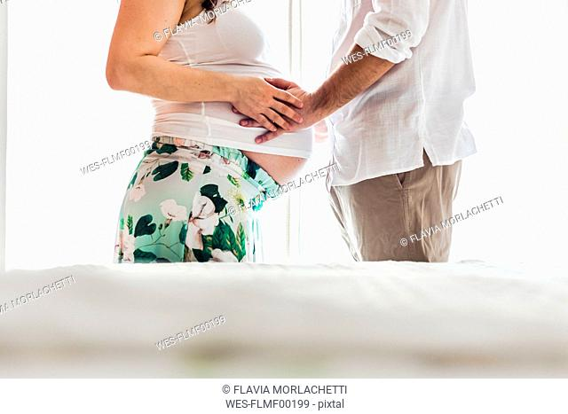Man touching belly of pregnant woman
