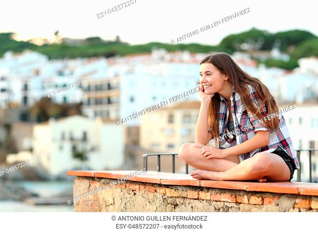 Pensive happy teenage girl contemplating hozizon sitting on a ledge in a coast town
