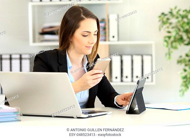 Office worker working with multiple devices on a desktop
