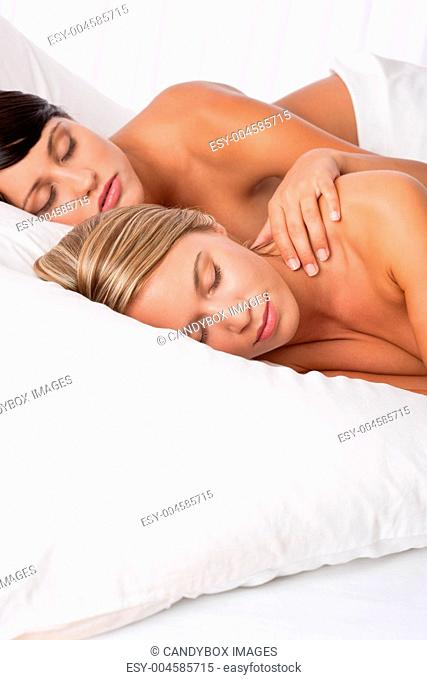 Two young women lying down in white bed