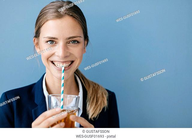 Portrait of a young businesswoman against blue background, drinking iced tea with a straw