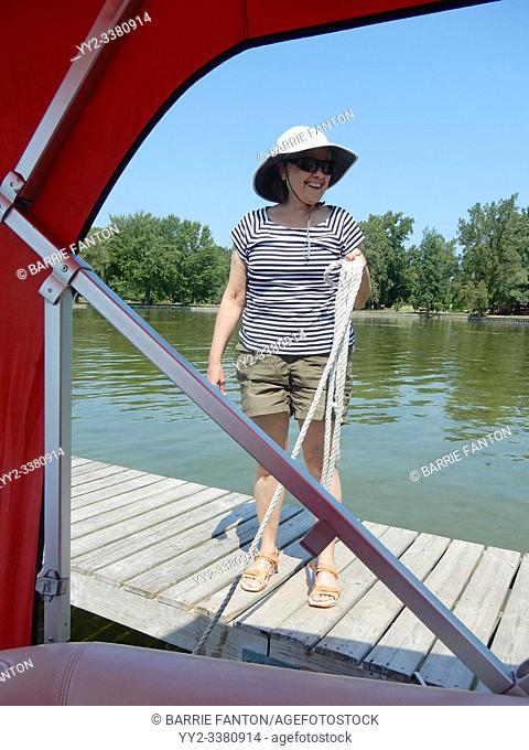 Senior Woman Holding Mooring Ropes for Boat, Conesus Lake, New York, USA