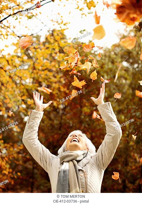 Older woman playing in autumn leaves