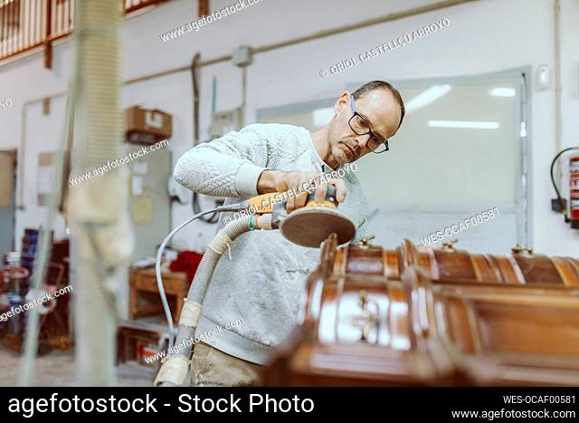 Male expertise polishing furniture with sander while standing at workshop