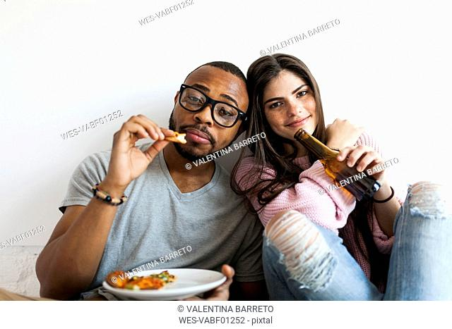 Young couple at home eating pizza and drinking beer