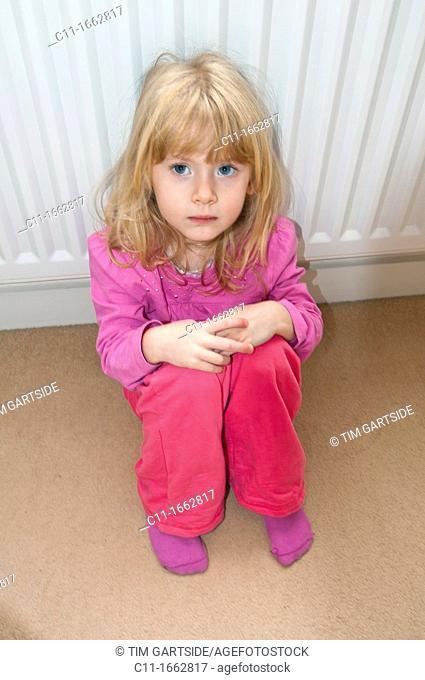 young girl sitting on floor looking worried