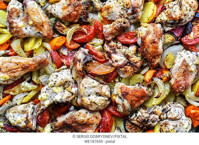 Chicken, cut into pieces, baked with vegetables in the oven close up
