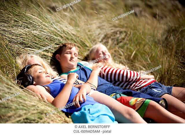Four friends relaxing in dunes, Wales, UK