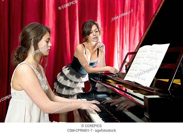 Two women performing a duet on a grand piano