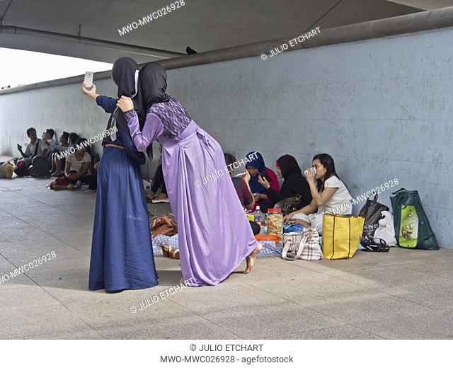 Migrant domestic workers enjoy a day off by the Bay side in Singapore