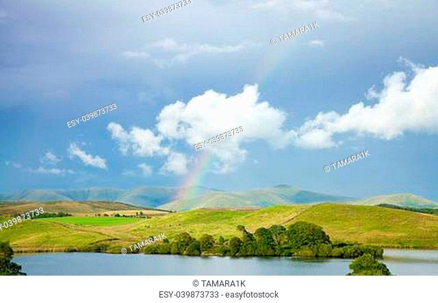 scottish landscape with clouds and rainbow over lake