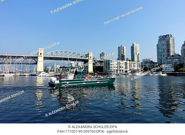 A whale watching boat can be seen on the False Creek in front of the Burrard Street Bridge in Vancouver, Canada, 29 August 2017
