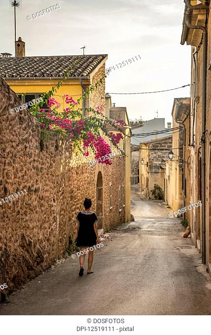 Woman walking down a narrow street; Alcudia, Mallorca, Balearic Islands, Spain