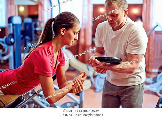 Fit girl exercising on facilities with her trainer near by